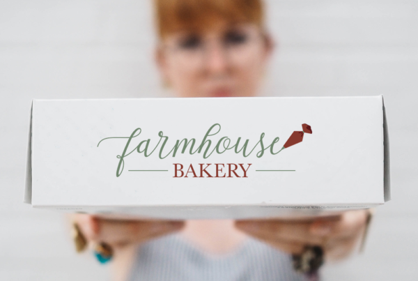 Farmhouse Bakery logo on a cakebox with a red headed women holding it